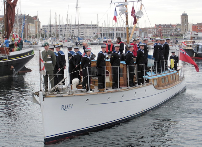 Royal Navy Sailors on the deck of Riis I, which was built in 1920 on the Clyde, salute upon leaving Dunkerque